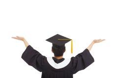 Estudiante de la graduación que lleva un birrete y manos abiertas Imagen de archivo libre de regalías
