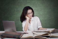Estudiante de la High School bastante secundaria que estudia en el escritorio Foto de archivo libre de regalías