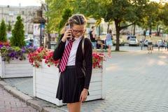 Estudiante de la High School secundaria del adolescente en la calle de la ciudad que habla en el teléfono Fotos de archivo libres de regalías