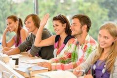 Estudiante de la High School secundaria que levanta su mano en clase Imagen de archivo libre de regalías
