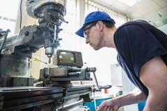 Estudiante de la ingeniería que usa el taladro grande Imagen de archivo libre de regalías