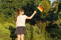 Estudiante de la niña que sostiene una bandera de Alemania, en el parque, parte posterior imágenes de archivo libres de regalías