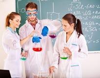 Estudiante de la química del grupo con el frasco. Fotografía de archivo libre de regalías