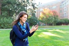 Estudiante de la raza mezclada texting Foto de archivo