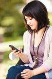 Estudiante de la raza mezclada texting Fotografía de archivo