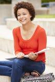Estudiante de la raza mixta que trabaja al aire libre Imagen de archivo