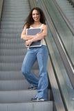 Estudiante de Latina que abraza en la escalera móvil Imágenes de archivo libres de regalías