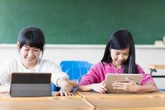 Estudiante de los adolescentes que mira la tableta en sala de clase Imagen de archivo libre de regalías