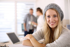 Estudiante de moda que sonríe en el escritorio de oficina Foto de archivo libre de regalías