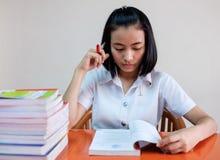 Estudiante de mujer adulta joven tailandés en uniforme que lee un libro Imagen de archivo libre de regalías