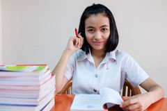 Estudiante de mujer adulta joven tailandés en uniforme que lee un libro Fotografía de archivo
