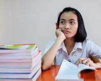 Estudiante de mujer adulta joven tailandés en uniforme que lee un libro Foto de archivo libre de regalías