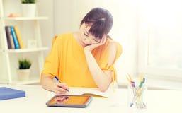 Estudiante de mujer asiático aburrido con PC de la tableta en casa Imagenes de archivo