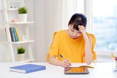 Estudiante de mujer asiático cansado con PC de la tableta en casa Foto de archivo libre de regalías