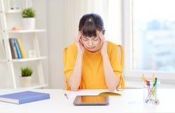 Estudiante de mujer asiático cansado con PC de la tableta en casa Imagen de archivo
