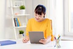 Estudiante de mujer asiático con PC de la tableta en casa Fotos de archivo