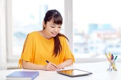 Estudiante de mujer asiático feliz con PC de la tableta en casa Imagen de archivo libre de regalías