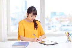 Estudiante de mujer asiático feliz con PC de la tableta en casa Fotos de archivo libres de regalías