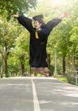 Estudiante de mujer asiático joven de la felicidad en su vestido de la graduación y casquillo de la graduación que lleva con e imagen de archivo