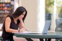 Estudiante de mujer asiático joven que se sienta en la tabla que trabaja con el ordenador portátil c Fotografía de archivo libre de regalías