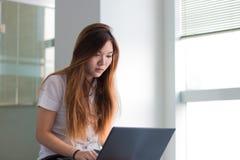 Estudiante de mujer asiático que trabaja en un ordenador portátil en la construcción cerca de ventana Imagen de archivo