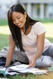 Estudiante de mujer asiático sonriente que estudia al aire libre Mirada a un lado Fotos de archivo