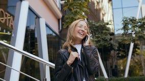 Estudiante de mujer atractivo joven en vidrios elegantes con un pelo largo que habla en el teléfono mientras que camina en el ur almacen de metraje de vídeo