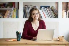 Estudiante de mujer atractivo sonriente con el ordenador portátil que mira la cámara, Imagen de archivo