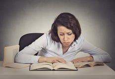 Estudiante de mujer con la expresión desesperada que mira sus libros Fotografía de archivo