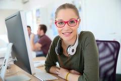 Estudiante de mujer con los vidrios rojos delante del ordenador Imagen de archivo