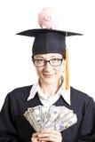 Estudiante de mujer de la graduación con las lentes que sostienen el dinero a de los dólares Fotografía de archivo libre de regalías