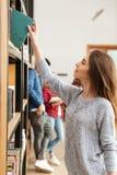Estudiante de mujer feliz joven que se coloca en libro de la biblioteconomía Fotografía de archivo libre de regalías