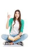 Estudiante de mujer hermoso joven sentándose con el libro Fotografía de archivo