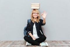 Estudiante de mujer joven alegre que sostiene los libros en la cabeza Imagen de archivo