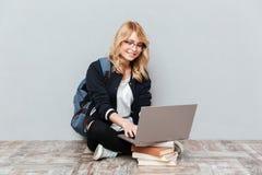 Estudiante de mujer joven alegre que usa el ordenador portátil Imágenes de archivo libres de regalías