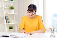Estudiante de mujer joven asiático feliz que aprende en casa Foto de archivo