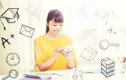 Estudiante de mujer joven feliz con smartphone en casa Fotografía de archivo libre de regalías