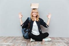 Estudiante de mujer joven feliz que sostiene los libros en la cabeza Imagenes de archivo