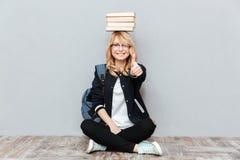 Estudiante de mujer joven feliz que sostiene los libros en la cabeza Imagen de archivo
