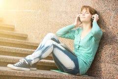 Estudiante de mujer joven hermoso con los auriculares Foto de archivo libre de regalías