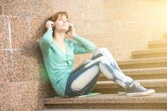 Estudiante de mujer joven hermoso con los auriculares Imagen de archivo libre de regalías