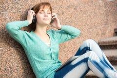 Estudiante de mujer joven hermoso con los auriculares Imagen de archivo