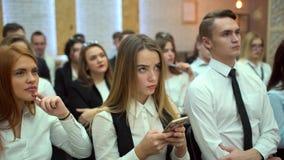 Estudiante de mujer joven que escribe el texto para el trabajo usando el smartphone dentro en la audiencia Visión desde de un gru metrajes