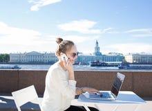 Estudiante de mujer joven que habla en el teléfono móvil durante trabajo sobre el ordenador portátil, sentándose cerca del río de Fotografía de archivo