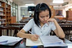 Estudiante de mujer joven que lee un libro con la tensión Foto de archivo libre de regalías