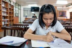 Estudiante de mujer joven que lee un libro con la tensión Fotografía de archivo