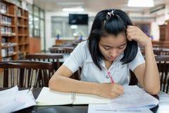Estudiante de mujer joven que lee un libro con la tensión Imagen de archivo