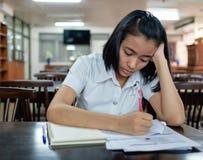 Estudiante de mujer joven que lee un libro con la tensión Imágenes de archivo libres de regalías