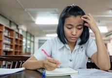 Estudiante de mujer joven que lee un libro con la tensión fotos de archivo