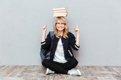 Estudiante de mujer joven que sostiene los libros en la cabeza y señalar Fotografía de archivo